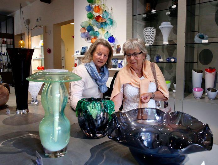 Bezoekers bekijken kunst in het glasmuseum.