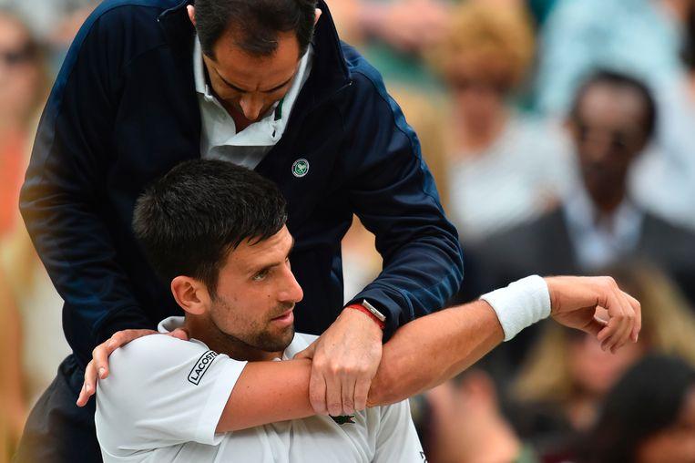 Novak Djokovic liet zich verzorgen na de eerste set, maar dat mocht niet baten.  Beeld AFP