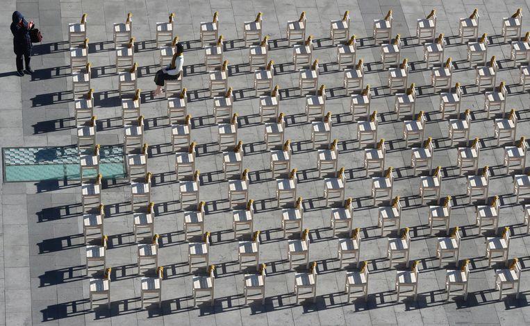 Een vrouw fotografeert het seksslavinnen-monument in Seoul. Op één stoel een beeld van een vrouw, de lege stoelen symboliseren de slachtoffers. Beeld AP