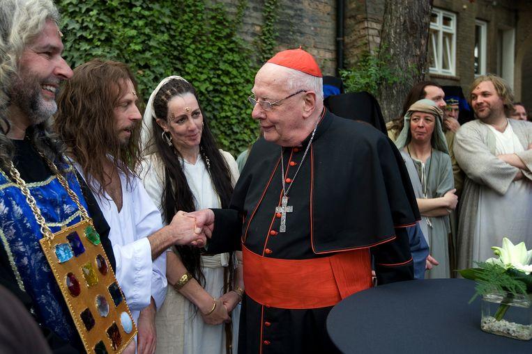 Kardinaal Simonis schudt in 2010 een van de hoofdrolspelers, René Geijbels (in de rol van Jezus), de hand na afloop van de premiere van de Passiespelen in Tegelen. Beeld Hollandse Hoogte/ANP