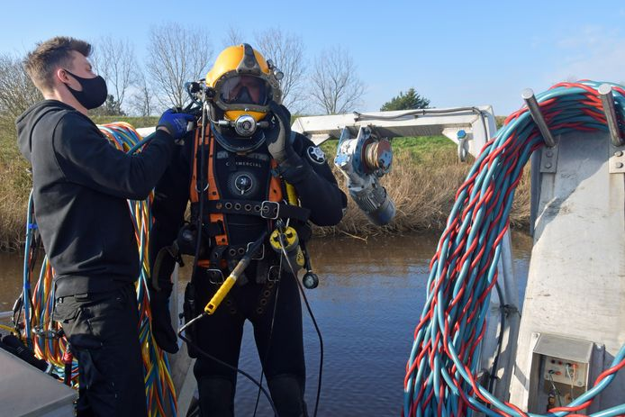 Het is elke keer een hele klus om de duiker in het pak te sjorren en alle aansluitingen goed aan te koppelen. Duiker Maurice krijgt hulp van collega Barry.