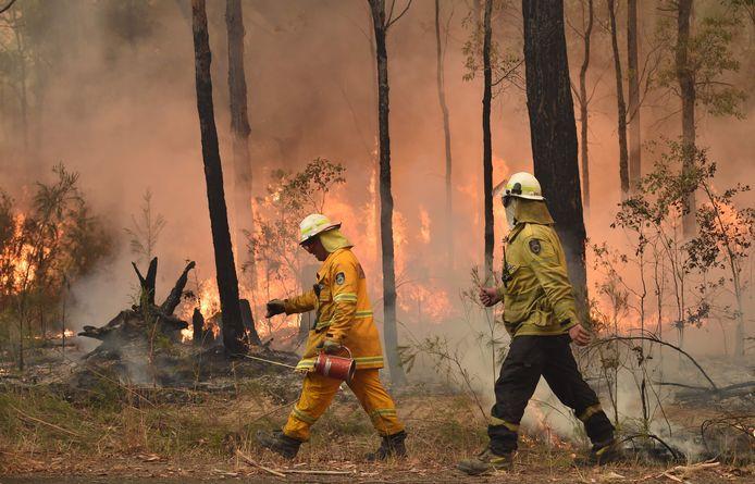 Brandweermannen creëeren een brandgang.