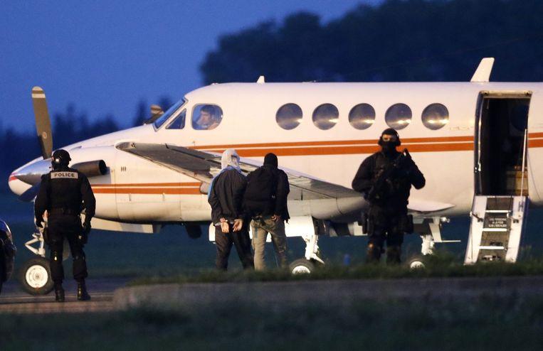 Een vermoedelijke jihadist wordt in Montpellier door de Franse politie geëscorteerd op een vliegtuig richting Parijs. Beeld epa