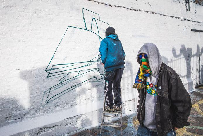 Binnen het uur werd het witte canvas terug overschilderd door kunstenaars van Wallin vzw.