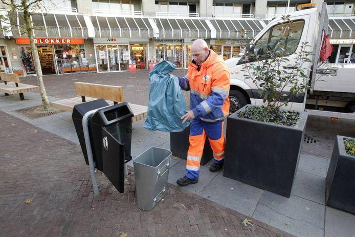 Piet van Dooren verwisselt de zak van een vuilnisbak in winkelcentrum Brouwhorst.foto Kees Martens
