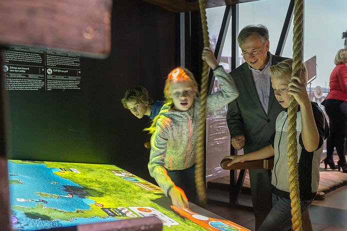 Directeur Willem Bijleveld van het Nederlands Openluchtmuseum in Arnhem bekijkt met een aantal kinderen de presentatie in het kader van de Canon van Nederland.
