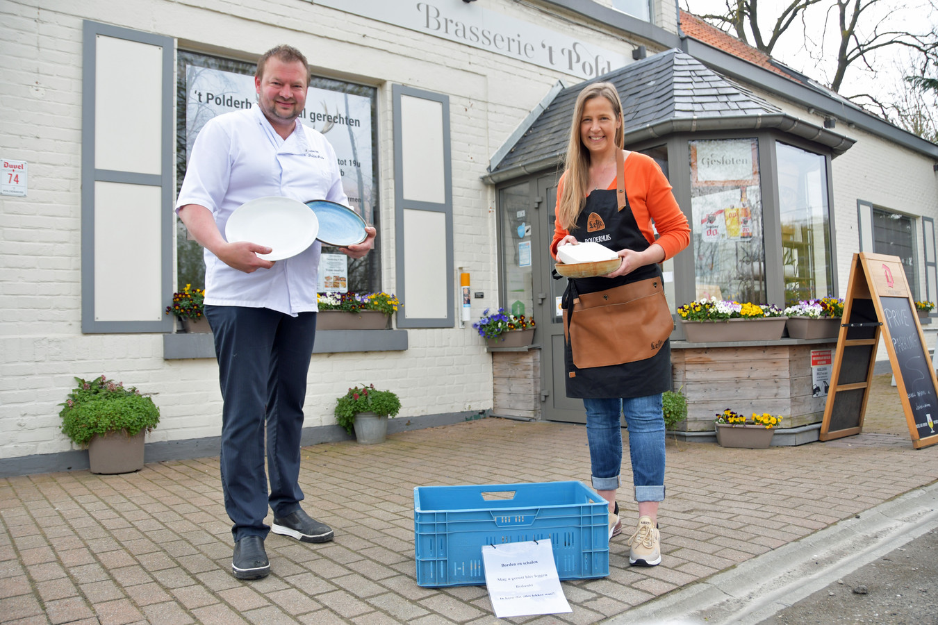 Philip Meul en partner Nathalie de Schrijver van Brasserie 't Polderhuis in Moerbeke bij de blauwe krat waar klanten nog steeds de geleende borden in mogen zetten. 't Polderhuis kreeg zaterdag gratis een nieuwe partij borden van een groothandel.