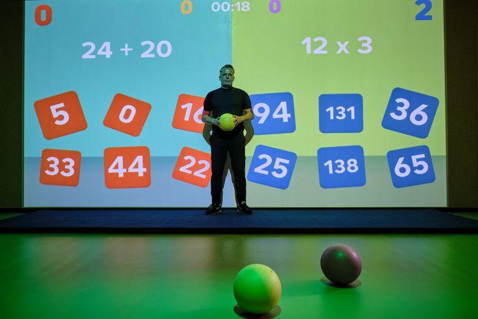 Robert van Gestel poseert voor een van de speelwanden in de sporthal op Sportpark Willem-Alexander.