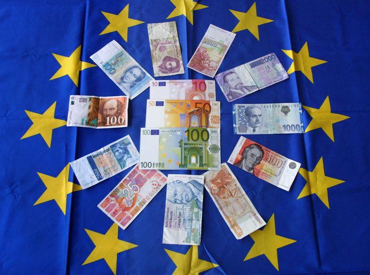 Eurobiljetten op een Europese vlag met daaromheen biljetten van oude Europese valuta. Beeld AFP