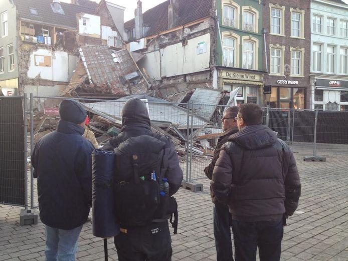 Voorbijgangers kijken naar de puinhoop van het ingestorte gebouw op de Markt.