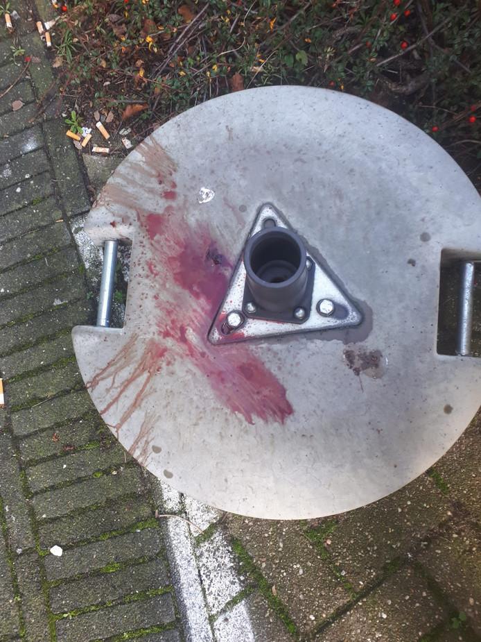 Op de voet van een parasol voor de school ligt bloed van het slachtoffer.