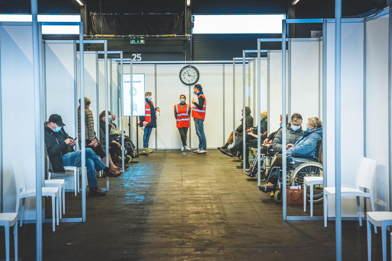 In Flanders Expo in Gent zitten 65+'ers klaar voor hun prik. De vaccinatiecentra verwelkomen de versnelling. Beeld Wannes Nimmegeers