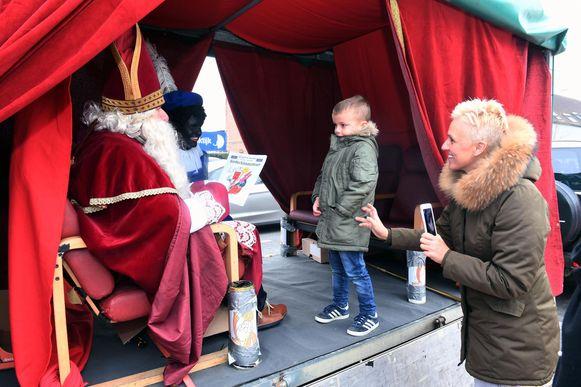 Sinterklaas en Zwarte Piet bekijken de mooie tekening van een jongen.