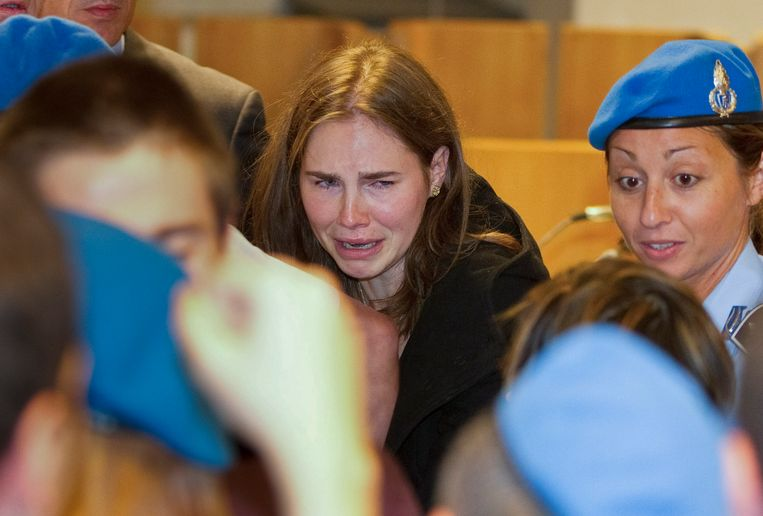 Amanda Knox cries as Raffaele Sollecito, left, walks in front of her, following the verdict that overturns her conviction and acquits her of murdering her British roomate Meredith Kercher, at the Perugia court, Italy, Monday Oct. 3, 2011. An Italian appeals court has thrown out Amanda Knox's murder conviction and ordered the young American freed after nearly four years in prison for the death of her British roommate. Knox collapsed in tears after the verdict was read out Monday. Her co-defendant, Raffaele Sollecito, also was cleared of killing 21-year-old Meredith Kercher in 2007. (AP Photo/Lapresse) ITALY OUT Beeld AP