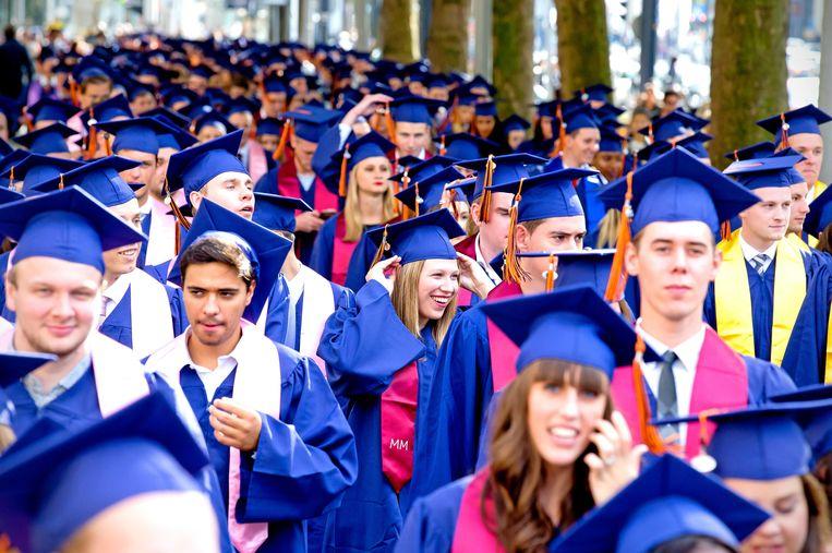 Afgestudeerden van de Rotterdam School of Management lopen in optocht door de binnenstad van Rotterdam.  Kom je er zonder minimaal een hogeschooldiploma niet tussen in het Nederlandse bestel? Beeld ANP