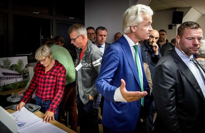 PVV-leider Geert Wilders heft zijn handen in onbegrip, terwijl dorpelingen de verbouwingsplannen van het azc bekijken.