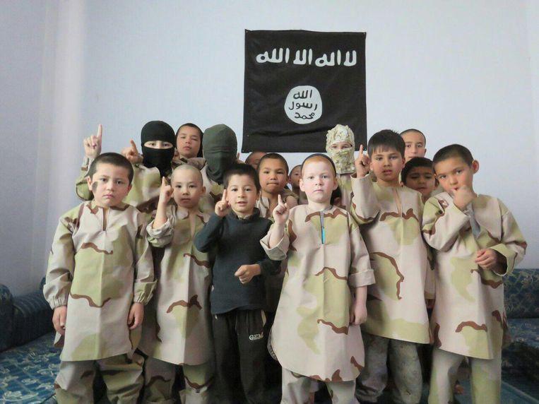 De zoon van Noerjana Ibrahimova uit Dagestan, Chadis staat recht voor, pal onder een IS-vlag. Hij is te herkennen aan zijn rode haar. Beeld via Noerjana Ibrahimova