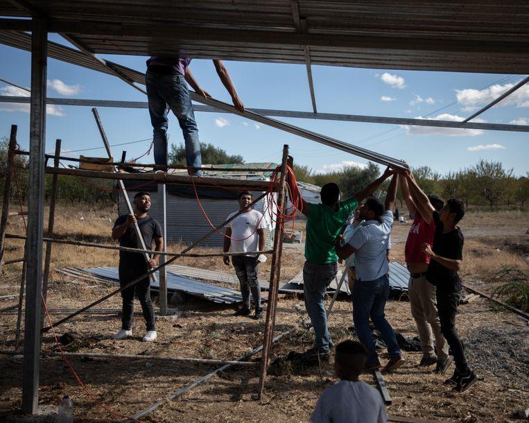 Inwoners van het 'Roma-getto' Girassol bouwen zelf een kerkje. Beeld Gonçalo Fonseca