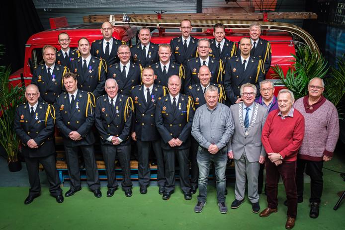 De gedecoreerde brandweerlieden poseren met burgemeester Geert van Rumund.