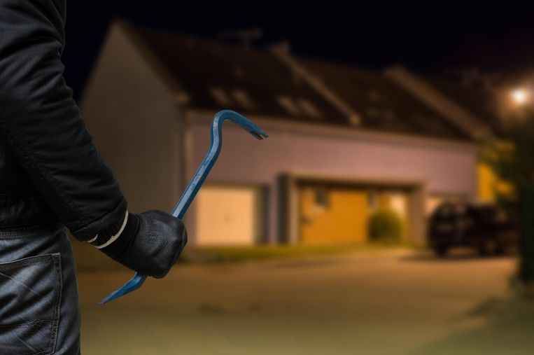 Crime concept. Burglar or robber with crowbar stands in front of the house at night.