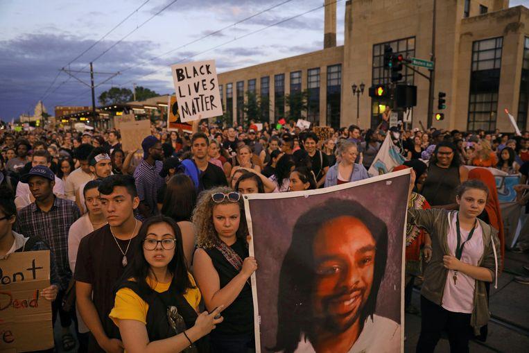 Demonstranten houden een portret van Philando Cstile omhoog terwijl ze door de straten van St. Paul marcheren. Beeld AP