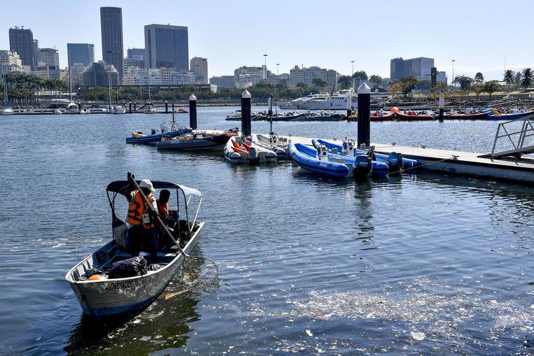 In de baai van Guanabara worden verwoede pogingen ondernomen om bagger uit het water te halen. Beeld belga