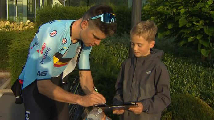 Een jonge fan krijgt een handtekening van Wout van Aert.
