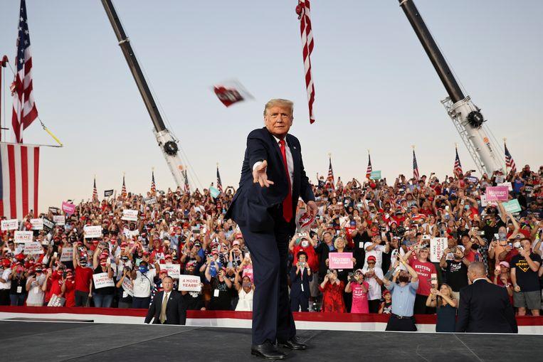 Trump gooit een mondkapje van het podium af tijdens zijn eerste campagnerally sinds hij positief testte op het coronavirus, in Sanford, Florida.  Beeld Reuters