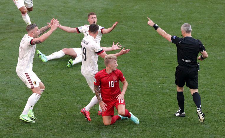 Björn Kuipers in actie tijdens de poulewedstrijd tussen België (in het wit) en Denemarken (rood). Beeld Reuters