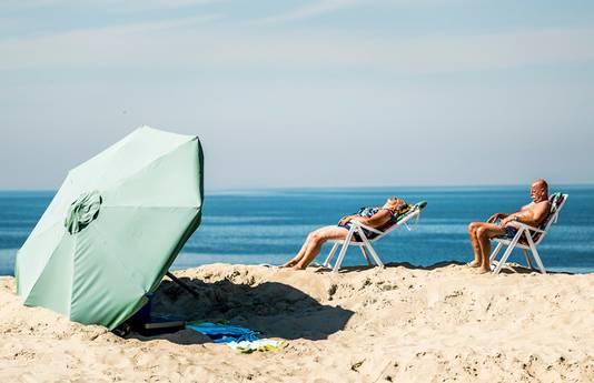 Mensen genieten van de zon op het strand nabij de Brouwersdam