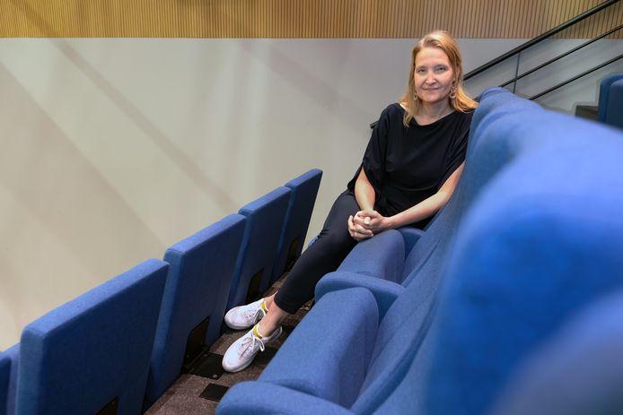 Directrice Charlotte Louwers in kleine zaal van van theater De Bussel in Oosterhout. Het lichte deel van de wand achter haar wordt donker geschilderd nu de voorstelling in het theater stil liggen.