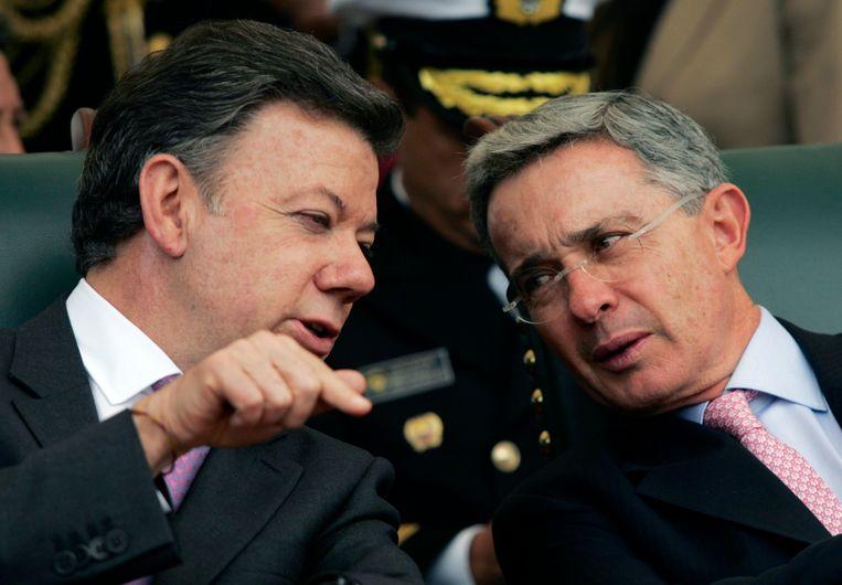 De gekozen president Juan Manuel Santos spreekt met vertrekkend president Alvaro Uribe op archiefbeeld uit 2010. Beeld REUTERS