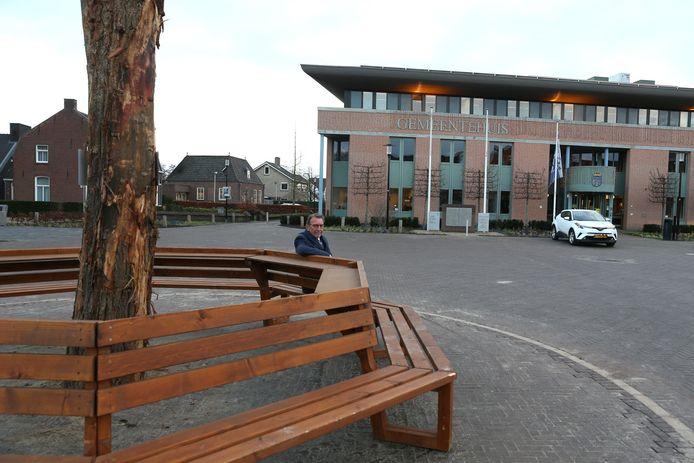 Wethouder Harry van Hal van de gemeente Haaren op het bankje op de plek waar straks de nieuwe kiosk komt te staan.