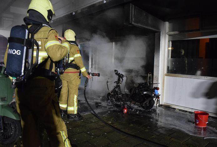 De brandweer blust de scooter bij de flat aan de Houtsmastraat in Doetinchem. De politieman die als eerste bij die brand was raakte zijn politiewagen kwijt aan een Doetinchemse joyrider. De man werd kort na de diefstal gepakt in Silvolde.