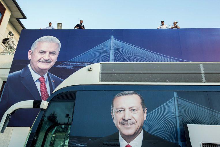 De hoofden van president Recep Tayyip Erdogan (beneden) en zijn burgemeesterskandidaat en vertrouweling Binali Yildirim (links) op een bus en een poster. Yildirim verloor de burgemeestersverkiezingen van Istanbul.  Beeld AFP