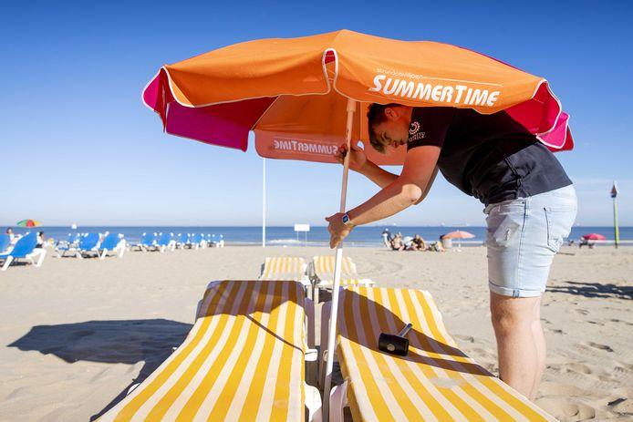 Een medewerker van een strandpaviljoen bereidt zich voor op een drukke dag.