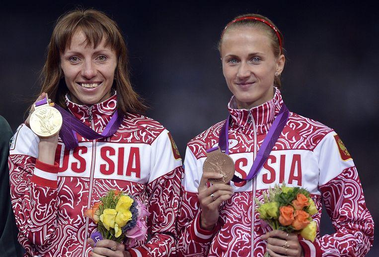 Maria Savinova en Ekaterina Poistogova tijdens de medailleuitreiking van de Olympische Spelen in 2012 Beeld EPA