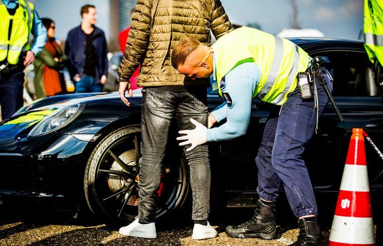 Een bestuurder wordt gefouilleerd tijdens een controle.  Beeld Hollandse Hoogte /  ANP