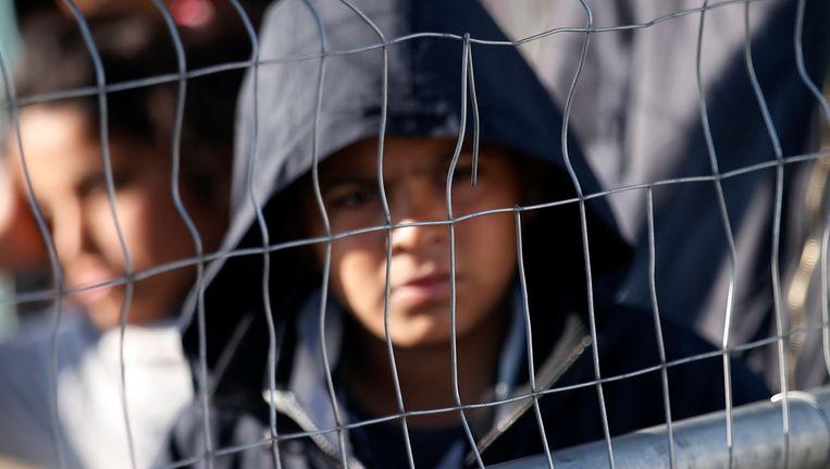 Een jonge migrant wacht op voedsel in een vluchtelingenkamp in Griekenland. Hij loopt de kans maandag te worden uitgezet naar Turkije, als de deal met Turkije een aanvang neemt Beeld AP