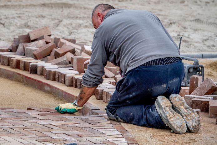 Een bouwvakker aan het werk in een nieuwbouwwijk in aanbouw