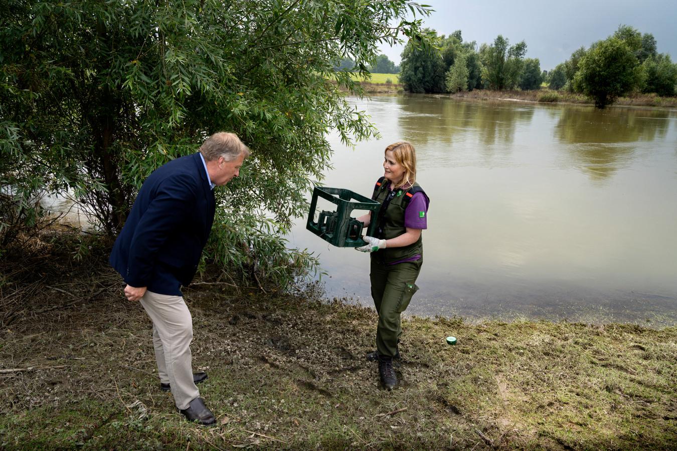 Boswachter Claudia Wessel toont aan wethouder Adrie Bragt wat er na het hoogwater allemaal in de Gamerensche Waarden is achtergebleven.
