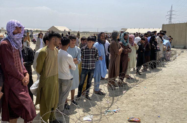 Afghanen wachten op evacuatie bij de luchthaven van Kaboel. Beeld EPA