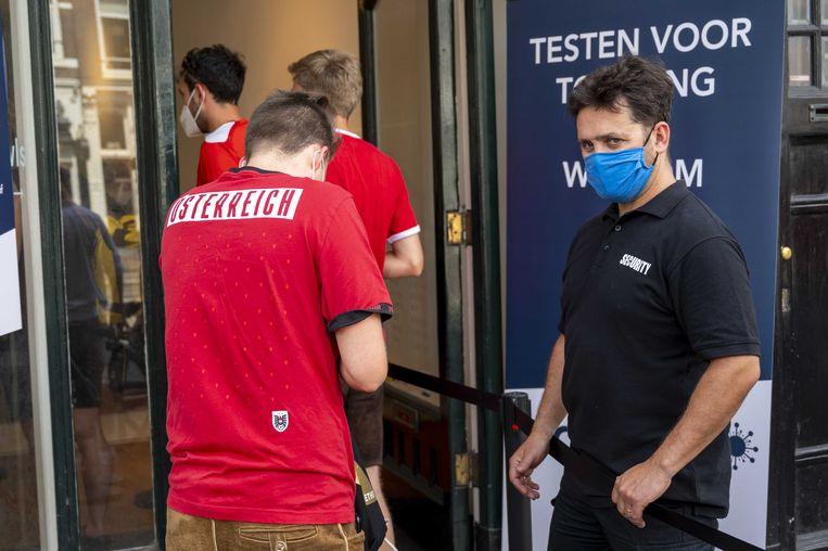 Een rij voor een testlocatie aan de Rozengracht. Voetbalfans die kaartjes hebben voor de EK-wedstrijd tussen Nederland en Oostenrijk moeten een negatief testbewijs kunnen laten zien. Beeld ANP