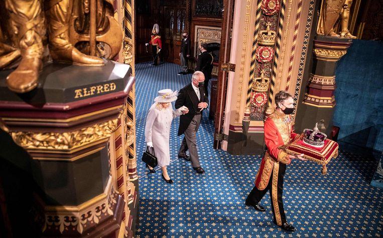 De Britse koningin Elizabeth en prins Charles lopen achter de kroon door de Royal Gallery, nadat de vorstin gisteren haar Queen's Speech had voorgedragen. In de Britse evenknie van de troonrede worden de regeringsplannen voor het komende jaar bekendgemaakt. Het was het eerste openbare optreden van Elizabeth sinds het overlijden van prins Philip.  Beeld AFP