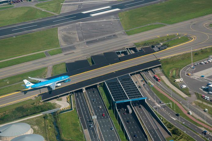 Een KLM-vliegtuig rijdt over de Schiphol Tunnel met de snelweg A4, richting  luchthaven Schiphol.