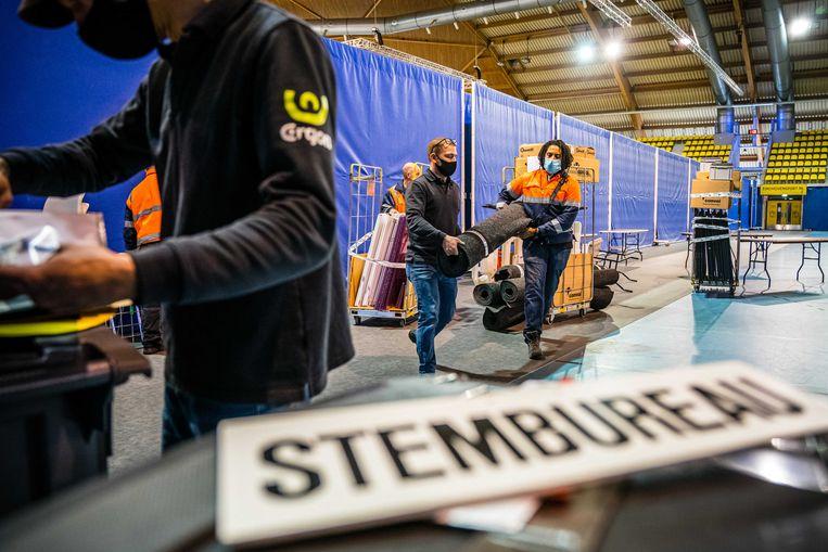 Voorbereidingen in een indoor sportcentrum dat dienst gaat doen als stemlocatie. Beeld ANP
