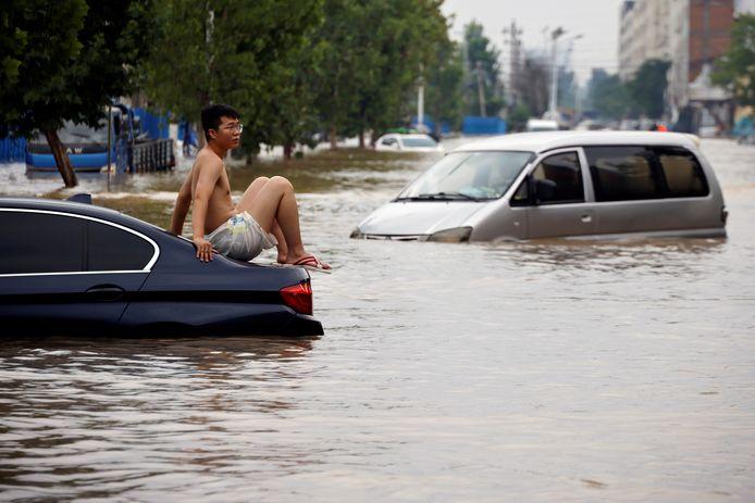 Een bestuurder wacht op hulp in de straten van Zhengzhou.