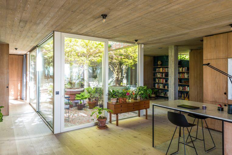 Een meterslang keukeneiland eindigt in een eet- en werktafel.Multifunctionaliteit is het codewoord in deze open woning.  Beeld Luc Roymans