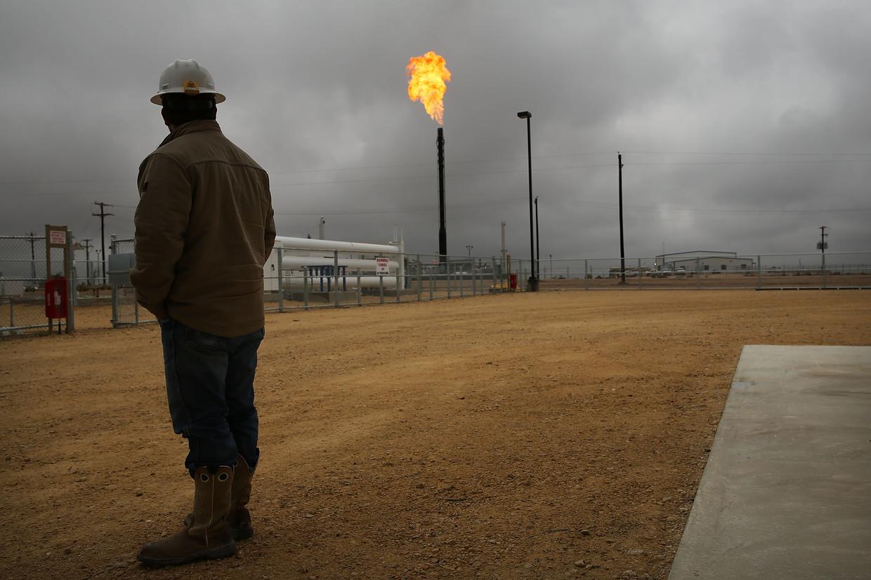 Een werknemer van Apache Corporations kijkt in het Texaanse Garden City naar de gasvlammen van het stoken van het overtollige aardgas. Beeld Getty