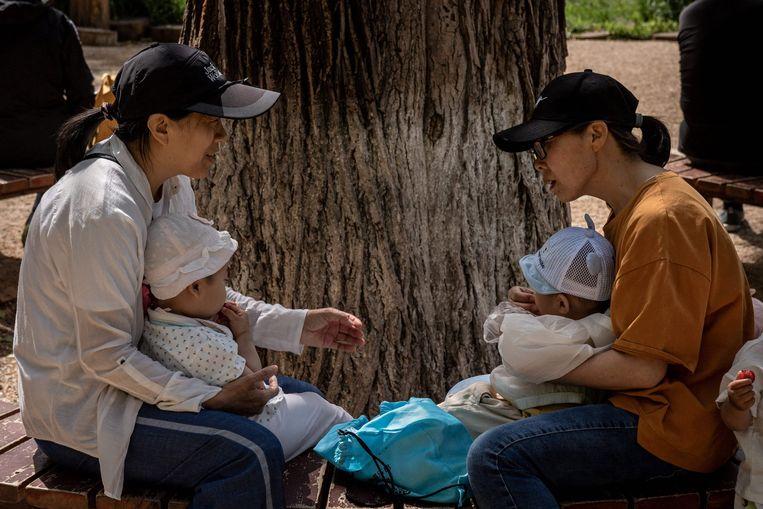 Twee moeders met hun kind in een park in Peking Beeld AFP